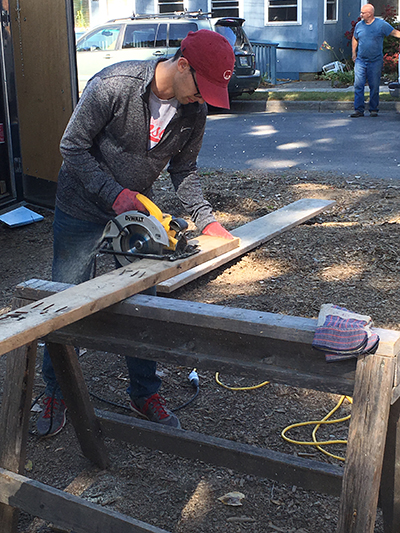 Photo of Matt Muskin sawing a piece of wood while working on a Habitat for Humanity project