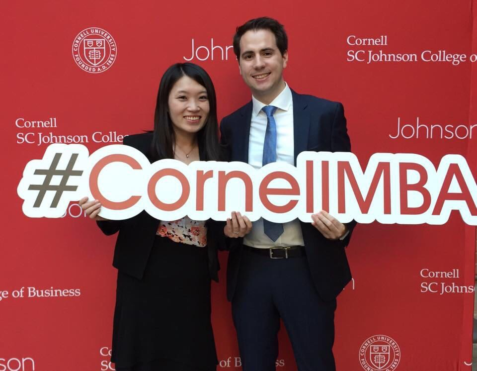 Photo of Nan and Nicolas holding a #CornellMBA sign