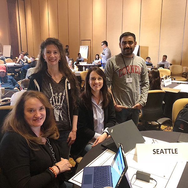 Photo of Catherine with her Seattle boardroom team working on an assignment