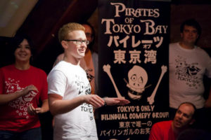 Photo of Jim next to a Pirates of Tokyo Bay banner