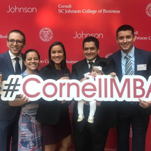 Photo of Carlos, Abby, and friends holding the #CornellMBA banner at orientation