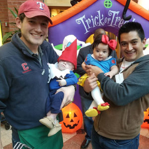 Photo of Carlos and Abby with another male student and child, dressed in Halloween costumes