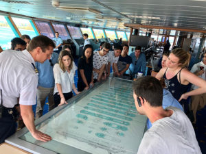 Students looking over a detailed drawing/map of the cruise ship