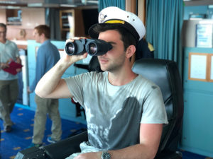 Photo of a student sitting in the captains chair with binoculars