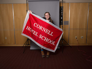 Photo of Marissa holding a banner that read Cornell Hotel School
