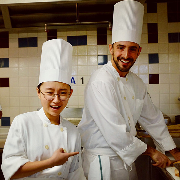 Photo of Nathan and a classmate wearing chef's hats