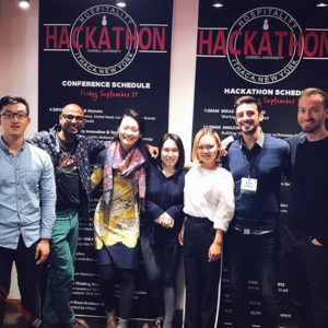 Photo of Nathan and teammates in from of Hackathon banners