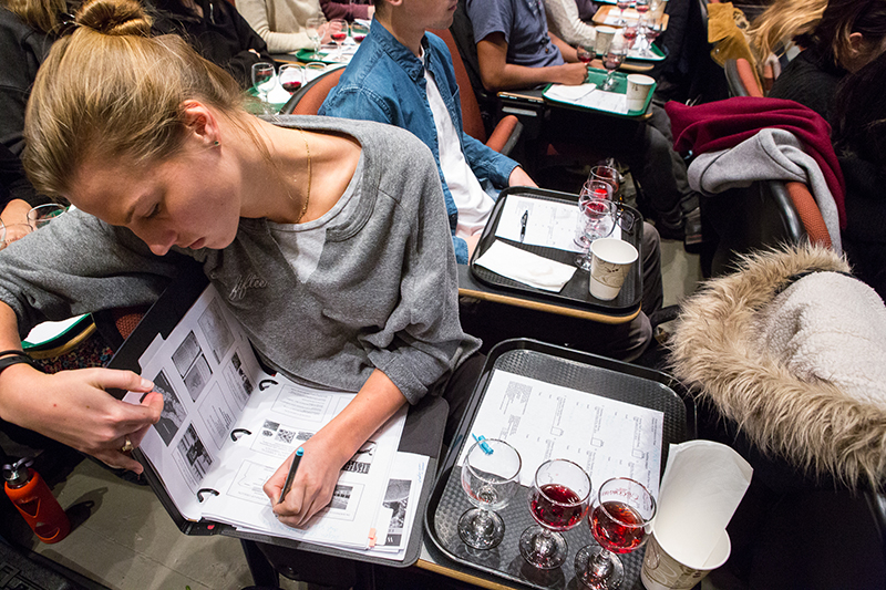 Photo of a student writing in her notebook with samples of wine nearby