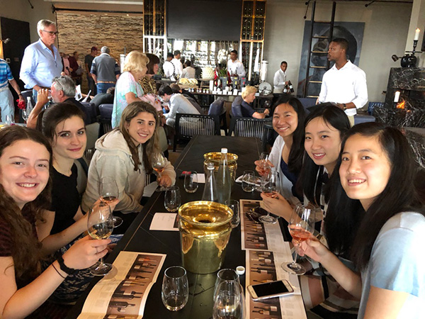 Photo of students sitting around a table with wine glasses and papers