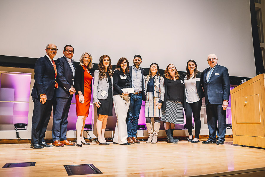 Photo of a group of students and Dean Walsh standing on stage
