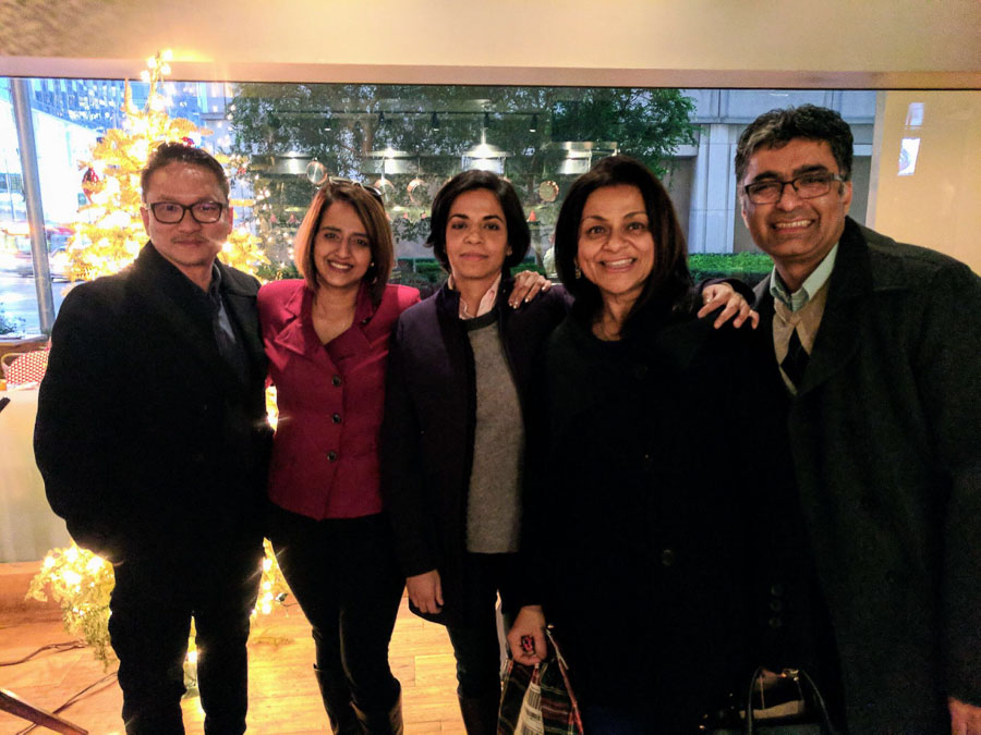 Photo of five people smiling and standing together