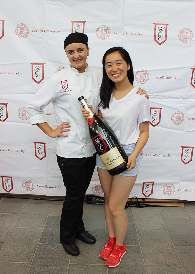 Photo of Eri and another student in from of a HEC banner