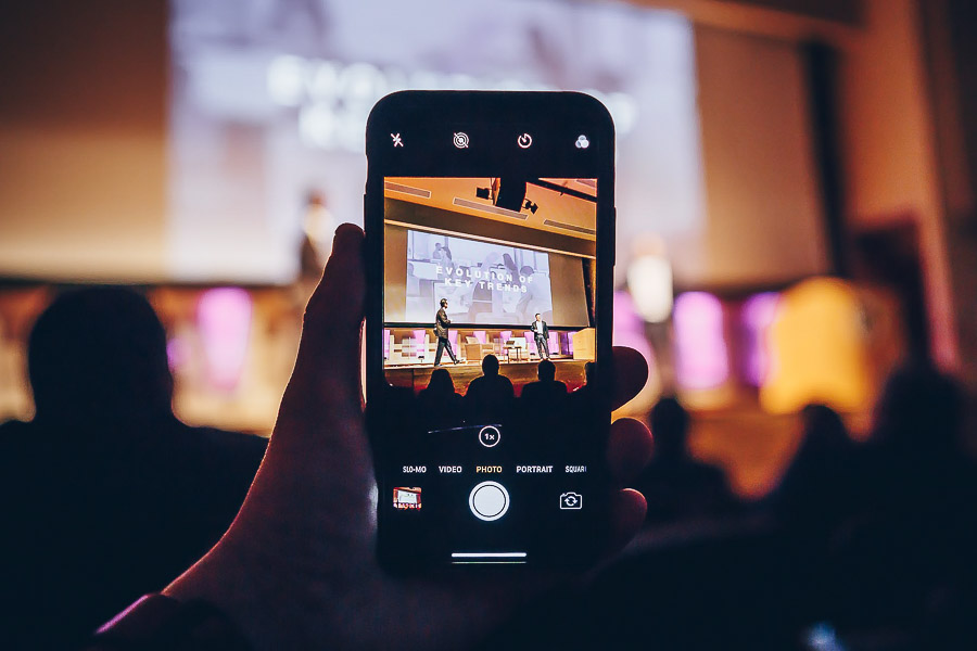 Photo of someone holding a phone and taking a photo of a presentation