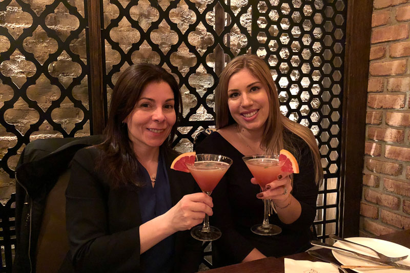 Photo of Katie holding a drink with a friend