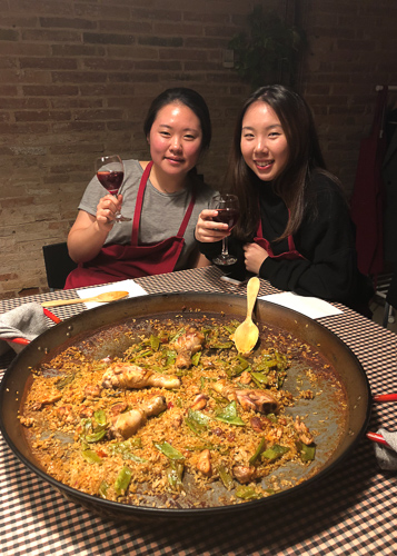 Photo of Nicole and a classmate holding wine behind a large bowl of paella