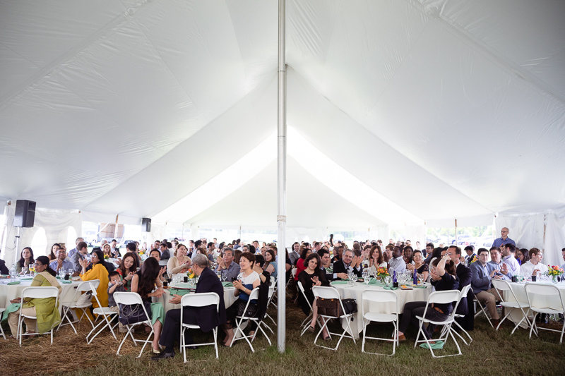 Photo of people seated under a tent