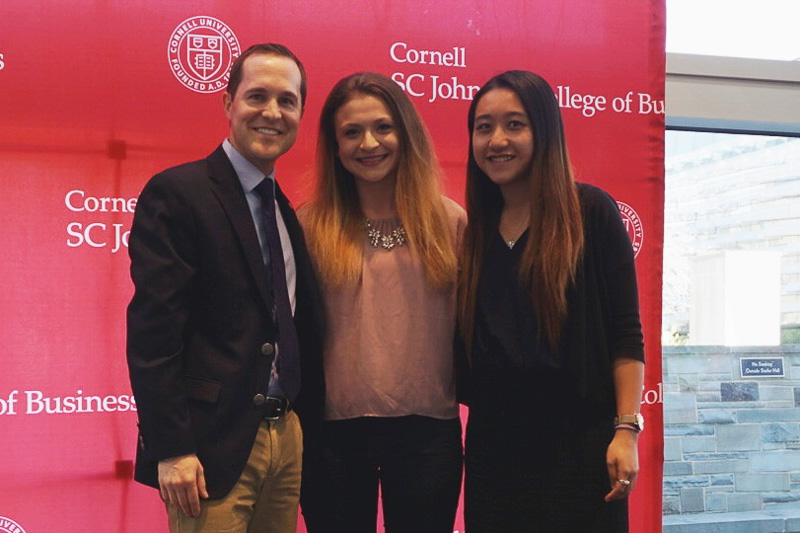 Photo of Andrew, Alexa, and Christie in front of a red backdrop