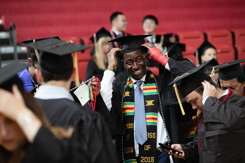 Photo of a graduate positioning his cap