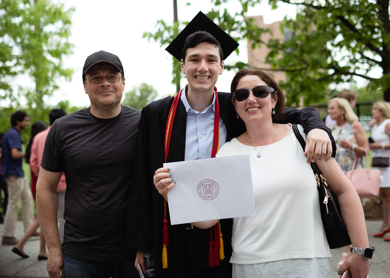 Photo of a graduate holding his certificate with his family