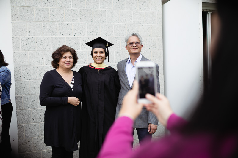 Photo of a person taking a photo of a graduate and his family