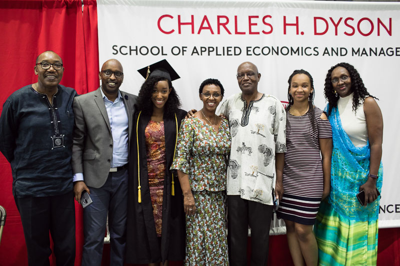 Photo of a graduate and her family in front of the Charles H. Dyson banner