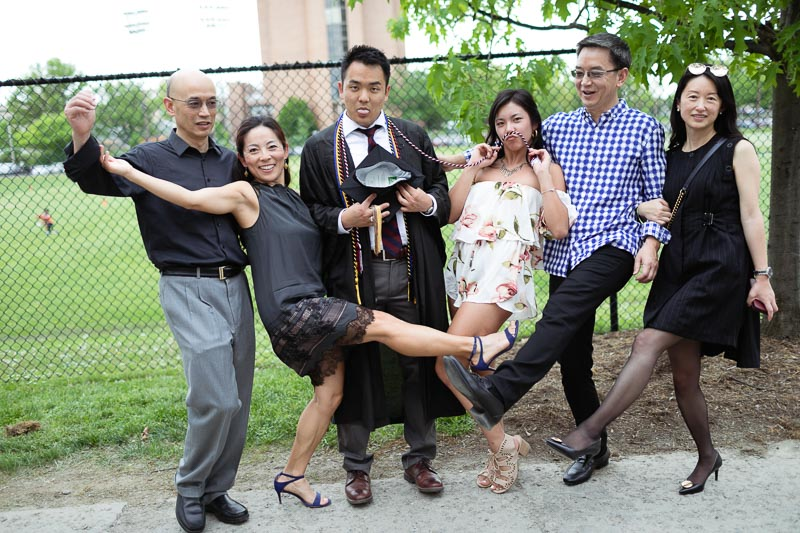 Photo of a family posing for a fun picture with a graduate