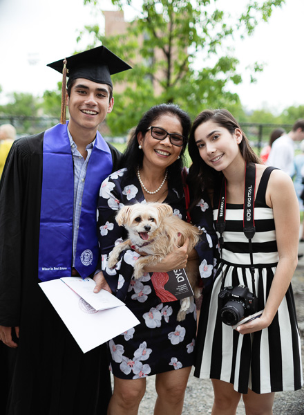 Photo of a graduate with his family and dog