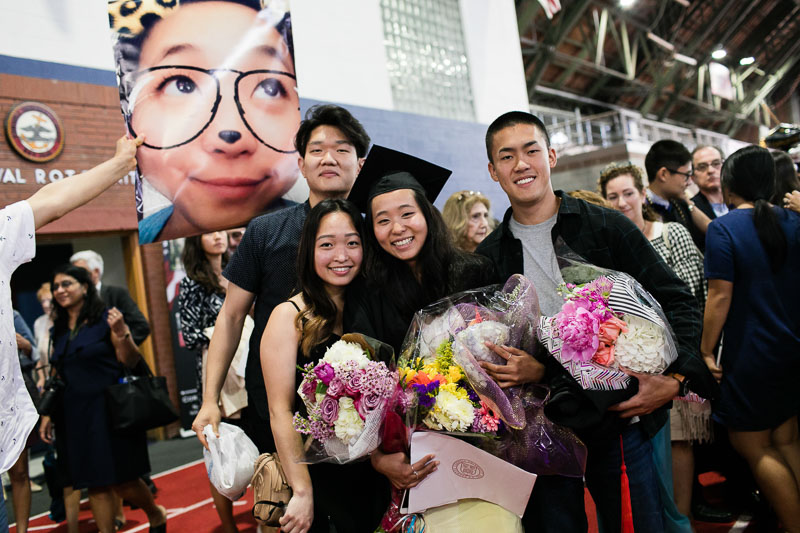 Photo of a graduate and their family holding flowers