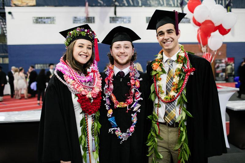 Photo of three graduates wearing Hawaiian necklaces