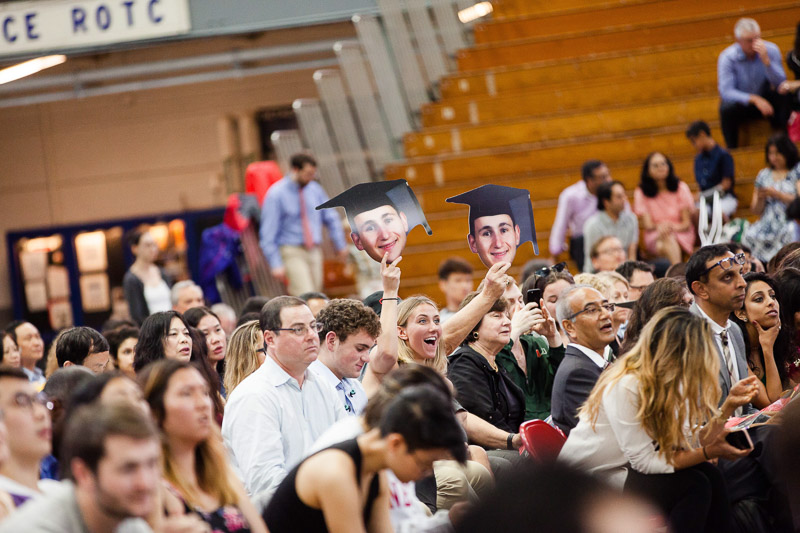Photo of a family holding cardboard cutout heads of their graduate