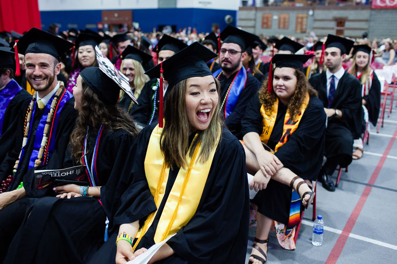 Photo of a graduate smiling in her seat