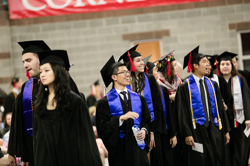 Photo of graduates looking for their families in the crowd