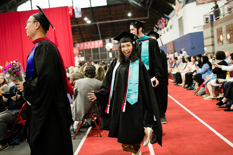 Photo of a graduate making a silly face while walking in