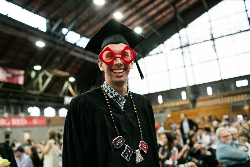 """Photo of a graduate wearing a """"grad"""" pair of glasses and necklance"""
