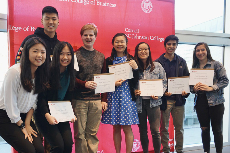 Photo of Jaimie with students holding certificates