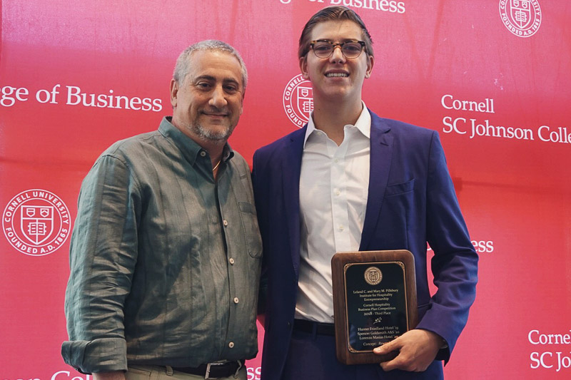 Photo of Neil and Hunter holding a plaque