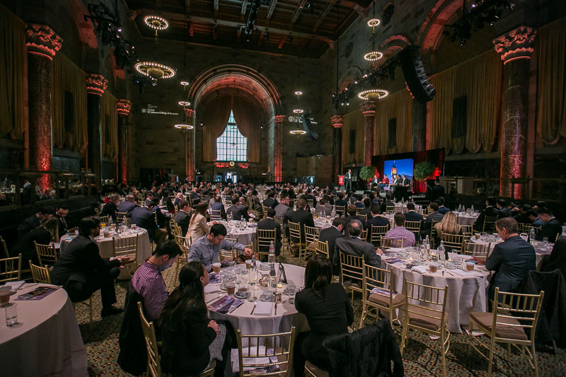 Photo of a packed ballroom with tables
