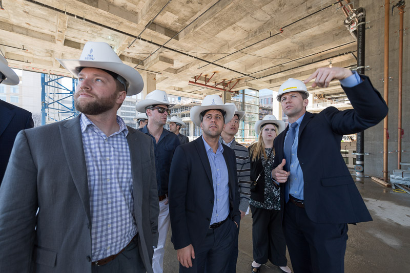 Photo of men wearing hard hats and cowboy hats at a construction site