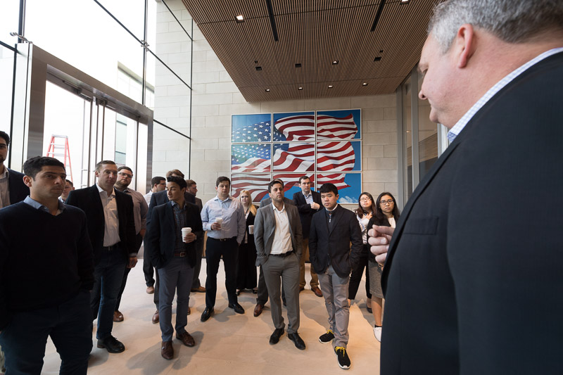 Photo of a group standing and listening to a speaker with an American flag in the background