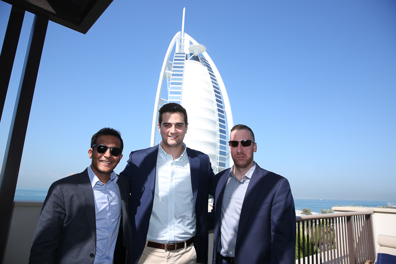 Photo of three men with a Dubai city building behind them