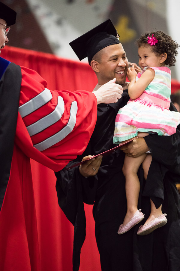 Photo of a graduate with his young daughter