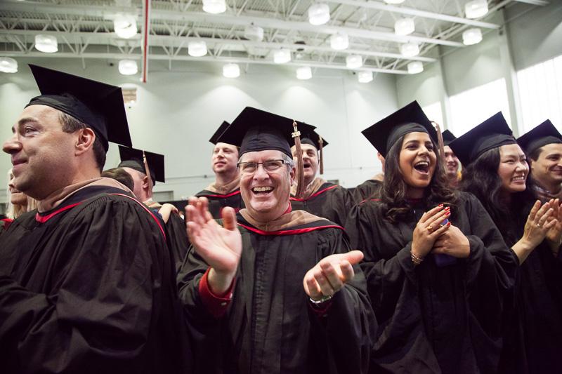 Photo of celebrating, clapping graduates