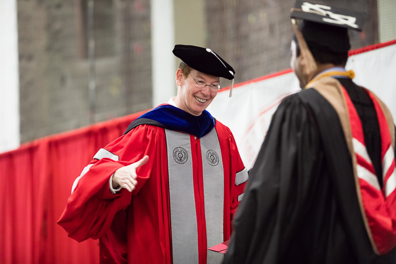 Photo of Mark Nelson shaking a graduate's hand