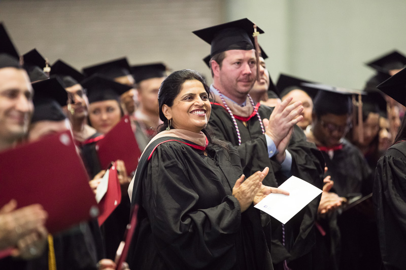 Photo of clapping, standing graduates