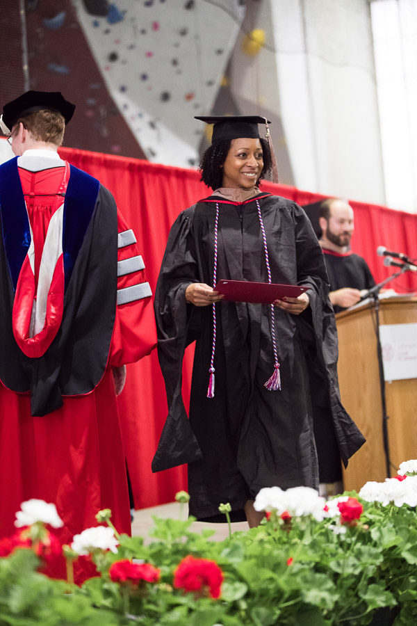 Photo of a graduate walking across the stage with her degree