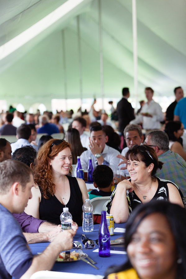 Photo of families sitting at table under a tent