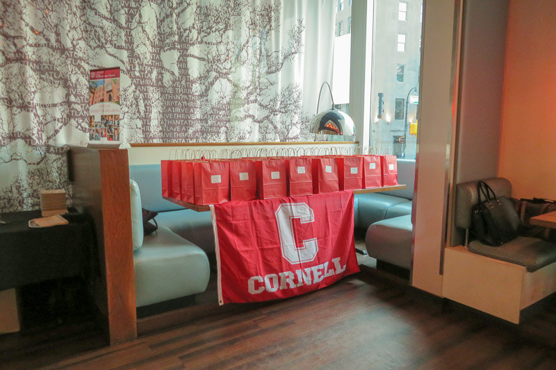 Photo of Cornell bags on a table with a Cornell banner