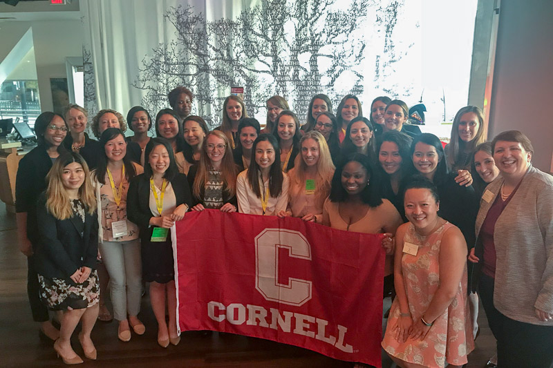 Photo of Cornell MBA women around a Cornell red banner