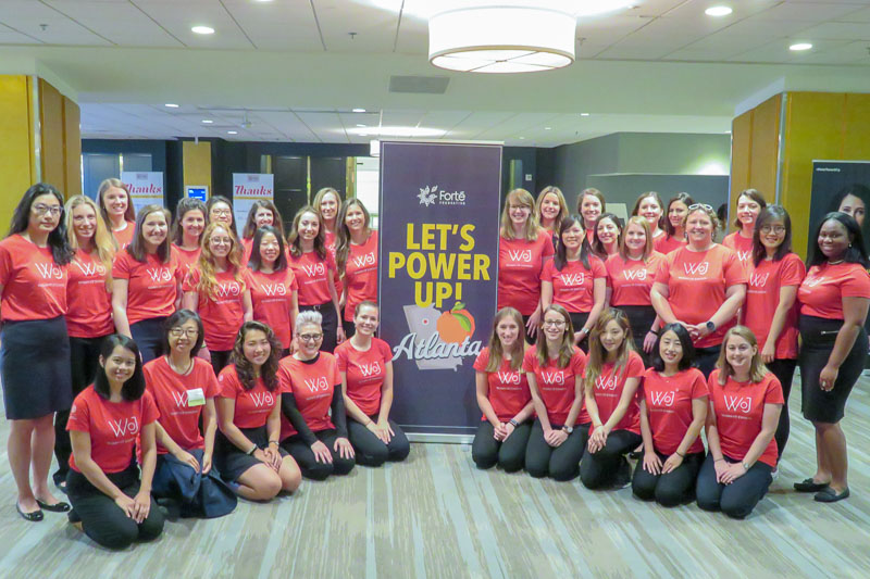 Photo of Cornell MBA women around a banner that says Let's Power Up!