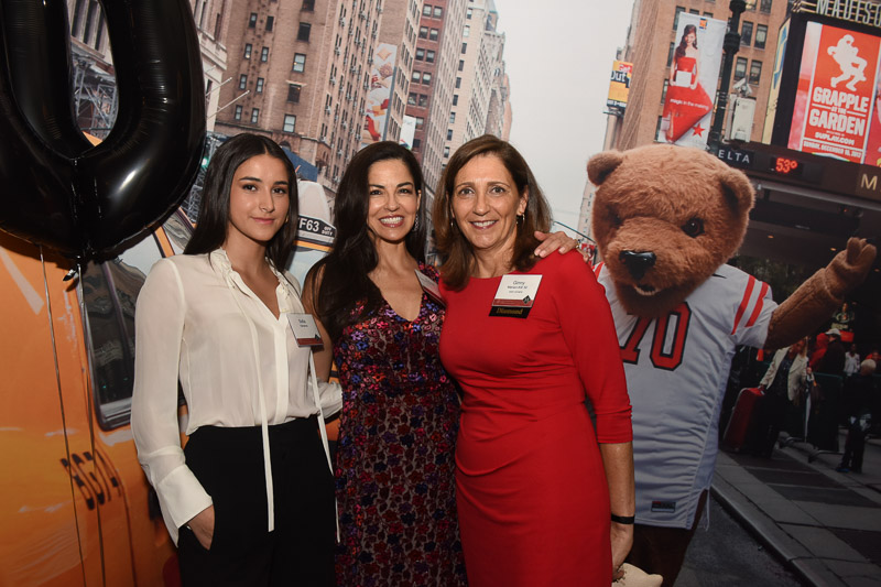 Photo of three women with Touchdown the bear outside the venue